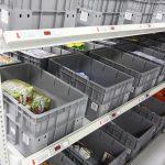 员工从流利货架拣选商品到按订单装货的周转箱中。